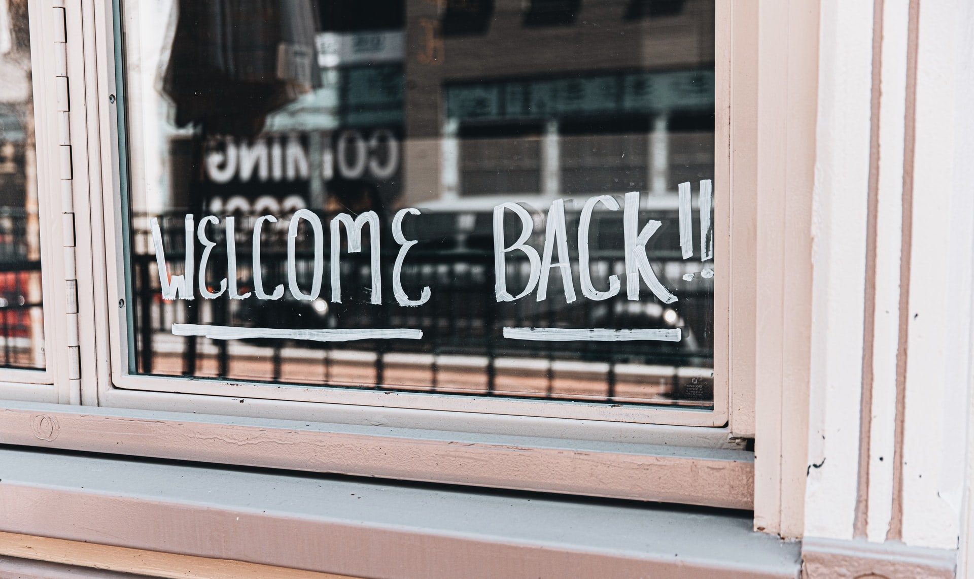 window sign says welcome back
