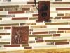 Hammered copper tile with elk design in custom back splash with hammered copper receptacle plug cover.