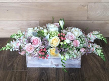 Rustic Gardens with lilac, freesia, hypericum berries, hydrangea and roses overflowing in a rustic wood container in Washington DC and Rockville MD, Palace Florists