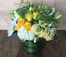 Sunny Yellows and Crisp Whites showcases roses, lilies and hydrangea in a leaf wrapped cylinder in Washington DC and Rockville MD, Palace Florists