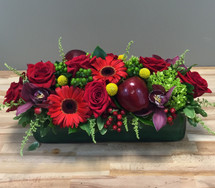 Lady in Red showcases red flowers such as roses, gerber daisies, orchids, hypericum berries and fresh red apples in a clear rectangular cylinder with a leaf wrap in Washington DC and Rockville MD, Palace Florists
