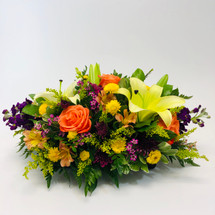 A lovely evening is a beautiful centerpiece showcasing stock, roses, lilies and alstromeria in low container in Rockville MD, Palace Florists