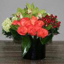 Orange Sherbert showcases orange roses, green hydrangea, hypericum berries, green cymbidium orchids wrapped with aspidistra leaves in a black ceramic cylinder