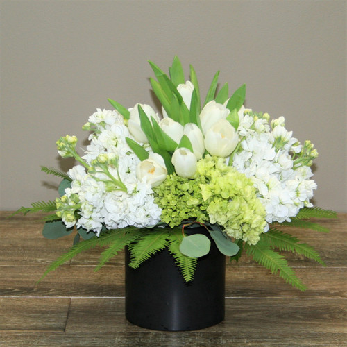 Whisper Whites  showcases an assortment of white and green flowers such as hydrangea, tulips, stock and beautiful foliage in a black ceramic cylinder in Washington DC and Rockville MD, Palace Florists