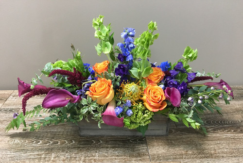 Rainbow Delight Centerpiece showcases roses, callas, bells of ireland, delphinium and other beautiful flowers in a rustic wood box in Potomac MD, Palace Florists