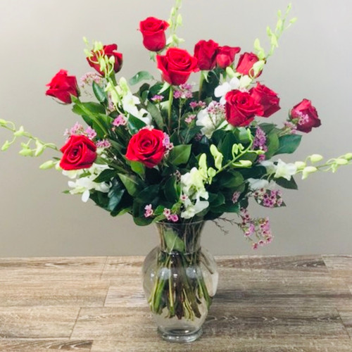 Crazy in Love showcases one dozen roses with white dendrobium orchids, curly willow and foliage hand designed in Rockville MD, Palace Florists