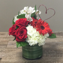 Love's Heart showcases red roses, red gerbers, white alstromeria and white hydrangea in a leaf wrapped cylinder with a wire token heart in Rockville MD, Palace Florists