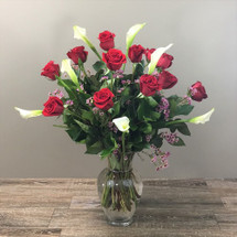 Elegant Love showcases one dozen long stemmed red roses with seven mini calla lilies with wax flower and foliage in Washington DC, Palace Florists