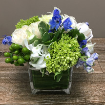 Under the Stars showcases white roses, hypericum berries,  green hydrangea and blue delphinium in Washington DC, Palace Florists