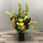 Fall Harvest showcases calla lilies, bells of Ireland, lilies,  sunset safari, protea and foliage in a black rectangle vase in Rockville MD, Palace Florists