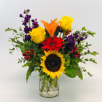 Farm Girl Chic showcases roses, stock, berries, sunflower and seeded eucalyptus in a clear cylinder in Rockville MD, Palace Florists