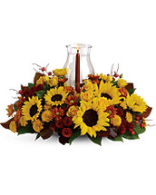 Sunflower Centerpiece features sunflowers, yellow spray roses, bronze and rust chrysanthemums, red berries, magnolia leaves and tapered candle inside a hurricane vase in Rockville MD, Palace Florists