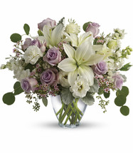 Woodside Wonders showcases lavender roses, white asiatic lilies, white lisianthus, white stock, lavender waxflower, and white sinuata statice accented with foliage in a glass vase in Rockville MD, Palace Florists
