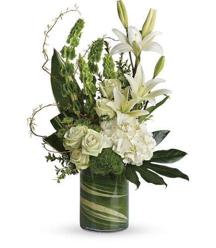 Botanical Beauty showcases flowers such as hydrangea, green roses, white asiatic lilies, green trick dianthus, bells of Ireland, green button spray chrysanthemums, curly willow, a variety of foliage in a cylinder vase in Rockville MD, Palace Florists.