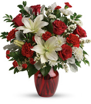 Visions of Love showcases fragrant white lilies and radiant red roses, hand-delivered in a ruby vase in Rockville MD, Palace Florists
