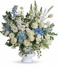 Treasured and Beloved showcase beautiful white and blue flowers such as hydrangea, roses, delphinium, snapdragons and stock in a white designer urn in Rockville MD, Palace Florists