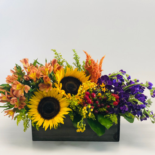 This beautiful bouquet is reminiscent of Mom's window box. Tulips, lilies, sunflowers and other flowers fill this rustic wooden box.