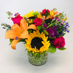 Garden Brights showcases sunflowers, lilies, roses, stock and other flowers in a cylinder vase in Rockville MD, Palace Florists