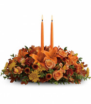 Family Gathering centerpiece features two orange taper candles surrounded by a fantastic array of fall flowers such as roses, lilies and alstromeria in Rockville MD, Palace Florists