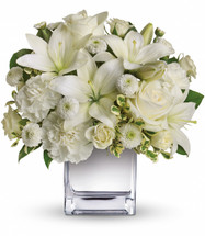 Peace and Joy showcases white roses, white spray roses, white Asiatic lilies, white carnations and white button spray chrysanthemums accented with assorted greenery in Rockville MD, Palace Florists