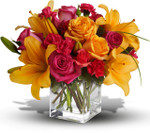 Uniquely Chic with orange roses, orange lilies, pink roses and pink mini carnations in a clear glass cube in Rockville MD, Palace Florists
