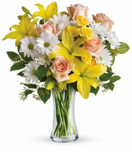 Daisies and Sunbeams showcases peach roses, yellow spray roses, yellow asiatic lilies, white daisy spray chrysanthemums and solidago accented with assorted greenery and hand-delivered in a glass gathering vase in Rockville MD, Palace Florists