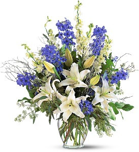 Sapphire Miracle Arrangement showcases delphinium, larkspur, lilies and eucalyptus in a clear glass vase in Rockville MD, Palace Florists
