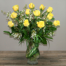 One dozen royal roses yellow accented with wax flower, coils of bear grass and beautiful foliage in clear glass vase in Washington DC and Rockville MD, Palace Florists