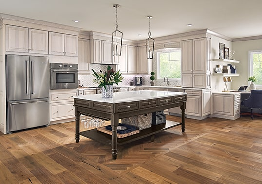 Traditional KraftMaid kitchen in Translucent Limestone finish with furniture island in Weathered Tavern finish