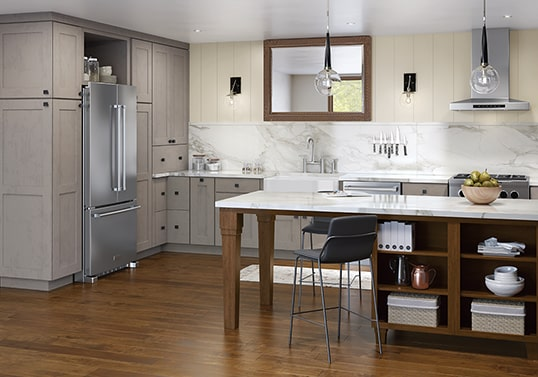 Transitional KraftMaid kitchen in Weathered River Rock finish featuring peninsula with furniture legs and open storage in Hoffman finish