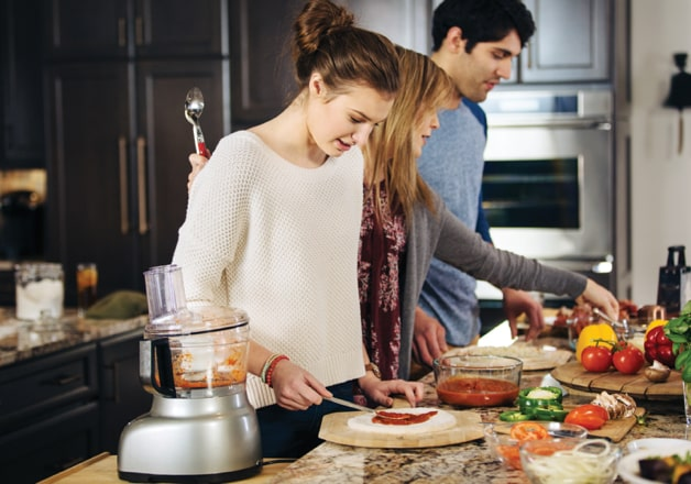 Couple and college-age daughter preparing meal at island in a transitional KraftMaid kitchen