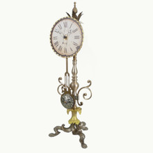 22H X 8D  Unusual time piece with pendulum Hand assembled and painted in cream, peridot and golden tones Quartz mechanism/AA battery    Your Cost:  $458.00  MSRP: $572.50