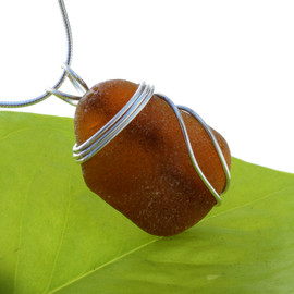 A large thick piece of amber brown sea glass set in our triple sterling silver setting.