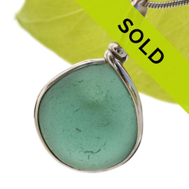 A beautiful thick piece of round aqua green sea glass set for a necklace in our Original Sea Glass Bezel© setting SORRY THIS SEA GLASS JEWELRY PIECE HAS BEEN SOLD!
