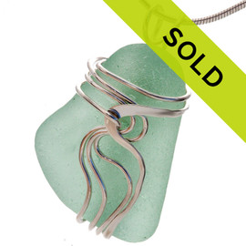 A pale aqua green sea glass set in our signature Waves© setting. Genuine beach found sea glass UNALTERED from the way it was found on the beach!