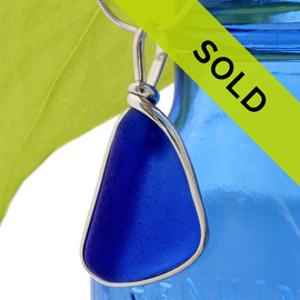 A triangular thick cobalt blue sea glass set in our Original Deluxe Wire Bezel© necklace pendant. This original By The Sea Jewelry setting that encases the glass in silver and leaves both front and back open so you can feel the texture of this antique top quality glass.  Sorry this piece has sold!