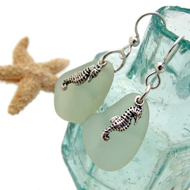 Natural seafoam green sea glass pieces are set with solid sterling seahorse charms and are presented on sterling silver fishook earrings.
