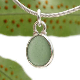 Perfect Oval olive green sea glass set in a sterling cinch bezel. Great for any charm bracelet or can be converted to a pendant or anklet.