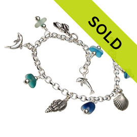 5 pieces of genuine beach found English Sea Glass in a flashed aqua blue and greens on a totally solid sterling silver bracelet finished with a sterling silver beach inspired charms.  Perfect for any sea glass lover.