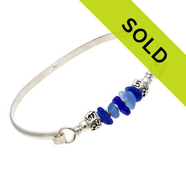 Five pieces of beach found sea glass in light and dark blue on this solid sterling silver half round sea glass bangle bracelet. Finished with solid sterling sea life beads to remind you more of the beach. Sorry this sea glass bracelet is no longer for sale.