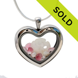 Small flashed pink sea glass pieces combined with a sandollar and pearls in a feminine heart shaped locket. Sorry this sea glass locket has been sold!