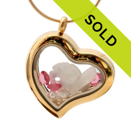 Small flashed pink sea glass pieces combined with a sandollar and pearls and pink tourmaline gems in a feminine heart shaped locket.