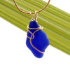 A nice irregular shaped piece of genuine blue sea glass in a gold deco inspired necklace setting.
