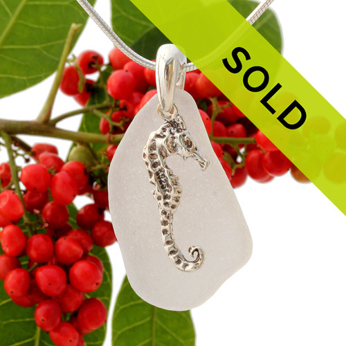A perfect piece of pure white sea glass with a solid sterling bail and large seahorse charm.