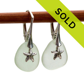A pair of natural surf tumble sea glass earrings in a seafoam green on sterling leverbacks and detailed with silver starfish charms. Sorry this sea glass jewelry item is no longer available.