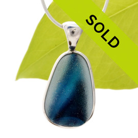 A vivid blue in a clear base. This piece was once the tip of a punty or pontil rod used to gather and work glass in the kiln. The color being worked was the rich brown at the bottom. Sorry this one of a kind sea glass jewelry piece has been sold!