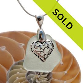 A nice piece of natural pale sea green sea glass necklace set on a solid sterling hand cast bail with a sterling silver heart in heart puff charm. Sorry this sea glass jewelry piece has been sold!