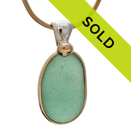 A stunning and large piece of unaltered beach found sea glass set in a classic timeless setting with mixed metals. Versatile and elegant! This piece has 3 metals, sterling silver, 14K goldfilled and a solid 14K embellishment. Sorry this sea glass jewelry piece has already been sold!