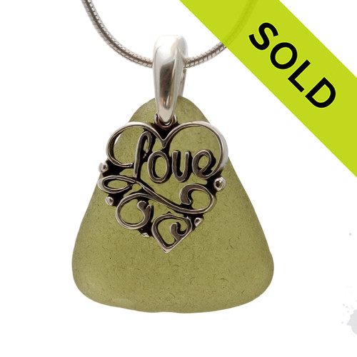 "A perfect piece of seaweed green genuine sea glass with a solid sterling bail and detailed ""Love"" heart charm. This piece comes complete with our sterling 1MM snake chain. SOLD - Sorry this Sea Glass Necklace is NO LONGER AVAILABLE!!!"