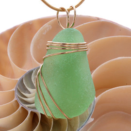 A stunning thick piece of yellowy seafoam green sea glass in a large necklace pendant.